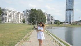 La muchacha joven y hermosa con el pelo rizado camina en el sendero en el parque y corresponde en el teléfono con sus amigos almacen de video
