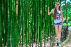 La muchacha joven y sonriente con el pelo largo se coloca cerca de un alto bambú foto de archivo