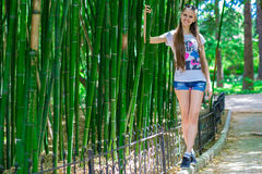La muchacha joven y sonriente con el pelo largo se coloca cerca de un alto bambú Imagenes de archivo