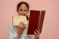 La muchacha judía lee el Haggadah de la pascua judía y Matzah de la consumición imagen de archivo
