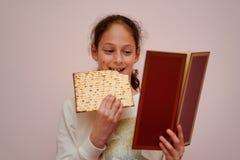 La muchacha judía lee el Haggadah de la pascua judía y Matzah de la consumición imagenes de archivo