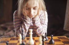 La muchacha juega a ajedrez Imagenes de archivo