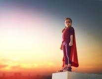 La muchacha juega al super héroe Fotos de archivo