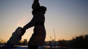 La muchacha juega con el bebé en la puesta del sol en invierno El circundar llevando a cabo las manos almacen de metraje de vídeo