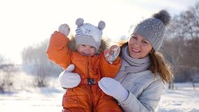 La muchacha juega con el bebé en soleado en invierno Llevar a cabo encendido las manos metrajes