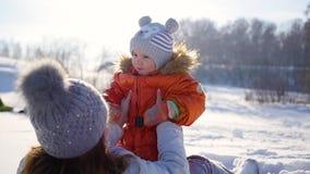 La muchacha juega con el bebé en soleado en invierno Llevar a cabo encendido las manos almacen de metraje de vídeo