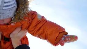 La muchacha juega con el bebé en soleado en invierno Llevar a cabo encendido las manos puente Cable-permanecido sobre el río en f almacen de metraje de vídeo