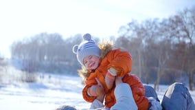 La muchacha juega con el bebé en soleado en invierno Llevar a cabo encendido las manos 3 vídeos en 1 almacen de metraje de vídeo