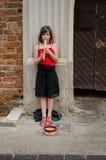 La muchacha juega con el tubo en la calle y pide limosnas Imagenes de archivo