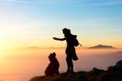 La muchacha juega con su perro en la montaña imagen de archivo