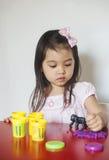 La muchacha juega el playdough foto de archivo