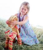 La muchacha juega en juegos del heno con una cabra wattled Fotografía de archivo libre de regalías