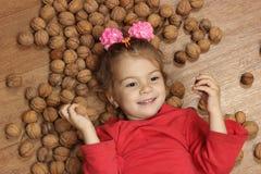La muchacha juega en un piso en un montón de nueces Imagen de archivo