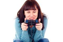 La muchacha juega fanáticamente en el juego video Imagenes de archivo