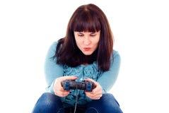 La muchacha juega fanáticamente en el juego video Fotografía de archivo