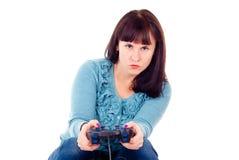 La muchacha juega fanáticamente en el juego video Foto de archivo libre de regalías