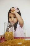 La muchacha juega los macarrones foto de archivo