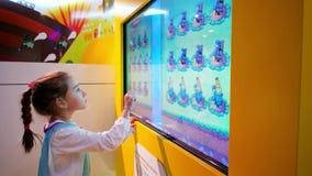 La muchacha juega, tecnología moderna como medios aprendiendo, movimiento de los niños sus fingeres a lo largo de la pantalla tác almacen de video