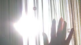 La muchacha jugó con sus manos a través de los rayos del ` s del sol Silueta de una muchacha metrajes