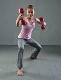 La muchacha juguetona adolescente está haciendo ejercicios con pesas de gimnasia para desarrollar los músculos en fondo gris Conc Foto de archivo