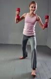 La muchacha juguetona adolescente está haciendo ejercicios con pesas de gimnasia para desarrollar los músculos en fondo gris Conc Fotografía de archivo libre de regalías
