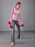 La muchacha juguetona adolescente está haciendo ejercicios para convertirse con los músculos de las pesas de gimnasia en fondo gr Fotografía de archivo libre de regalías