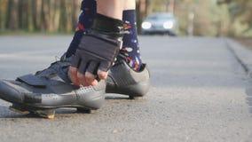La muchacha juguetona aprieta los zapatos de ciclo del camino negro y gris antes de entrenar C?mara lenta metrajes