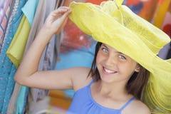 La muchacha juguetona intenta encendido el sombrero amarillo en el mercado Fotos de archivo libres de regalías