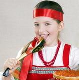 La muchacha lame una cuchara con el caviar rojo Fotos de archivo libres de regalías