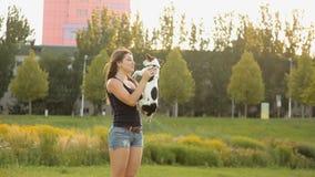 La muchacha lanza el perro para arriba El caminar con un perro en el parque almacen de video