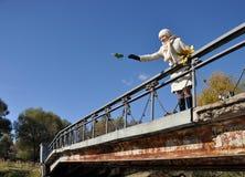 La muchacha lanza la hoja del arce al agua del puente Imagen de archivo libre de regalías