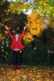 La muchacha lanza las hojas de otoño hacia arriba Fotos de archivo libres de regalías