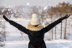 La muchacha lanza nieve en aire durante invierno Fotografía de archivo libre de regalías
