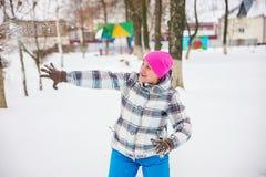 La muchacha lanza la nieve en el parque Imagen de archivo libre de regalías