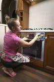 La muchacha lava el horno en la cocina Foto de archivo libre de regalías