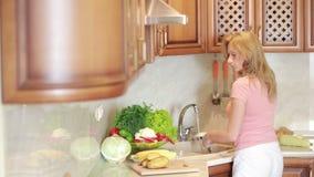 La muchacha lava la patata Verduras en la tabla de cocina almacen de video