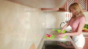 La muchacha lava las uvas Verduras en la tabla de cocina almacen de metraje de vídeo