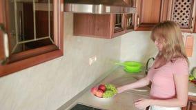 La muchacha lava las uvas Verduras en la tabla de cocina Tomates y col metrajes