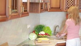 La muchacha lava las uvas Verduras en la tabla de cocina Tomates y col almacen de metraje de vídeo