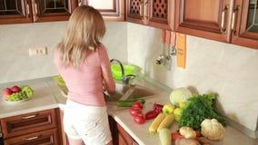 La muchacha lava los pepinos Verduras en la tabla de cocina metrajes