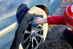 La muchacha lava la suciedad de las ruedas del coche fotos de archivo