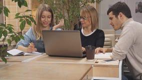 La muchacha le dice compañeros de trabajo mirar su ordenador portátil metrajes