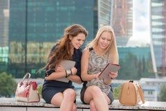 La muchacha le muestra las fotos del amigo Imagen de archivo libre de regalías