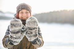 La muchacha le muestra las manoplas en la nieve imagen de archivo