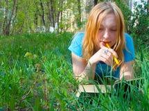 La muchacha lee el libro. Imagen de archivo