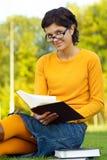 La muchacha lee el libro en césped Imagen de archivo