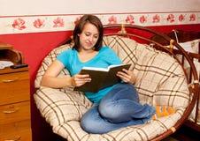 La muchacha lee el libro en una butaca Fotos de archivo libres de regalías