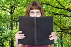 La muchacha lee el libro grande y el bosque verde del verano Fotografía de archivo