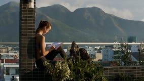 La muchacha lee el libro que se sienta en miradas de la terraza en el hombre de la cámara