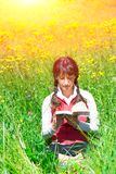 La muchacha lee el libro que se sienta en un prado Imagen de archivo
